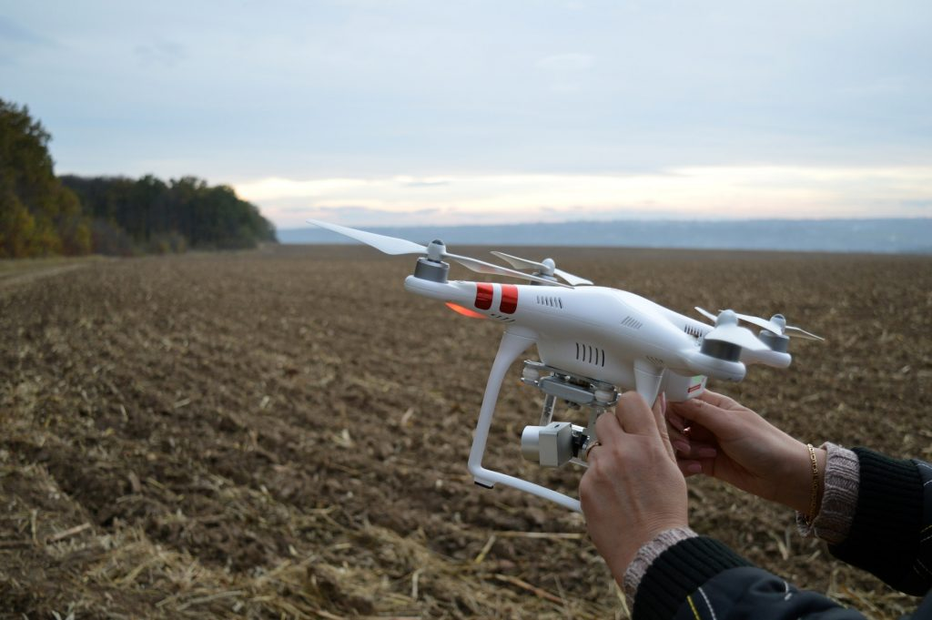 person-holding-dji-phantom-3-quadcopter-drone-at-open-field-1545754